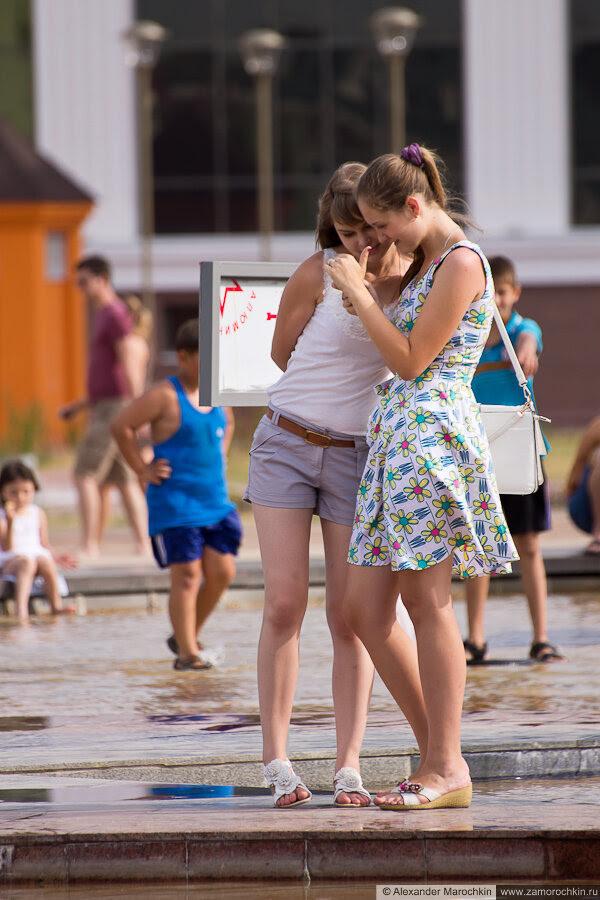 Девушки рассматривают фотографии у фонтана