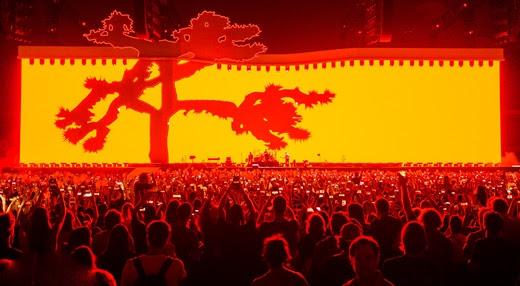 Bela imagem com a 'Joshua Tree' em destaque; pelo tamanho dos músicos se vê a imensidão do telão