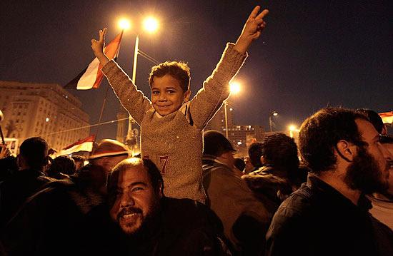Criança levanta os braços em comemoração pela renúncia de Mubarak na praça Tahrir, centro do Cairo