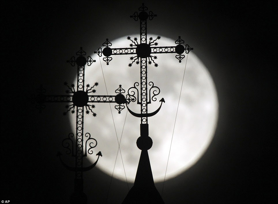 Ornate: The full moon rises behind a steeple with crosses of an Orthodox church in the town of Novogrudok, Belarus