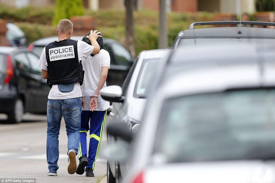 Um policial francesa prende um homem após uma busca em uma casa na cidade de Normandy de Saint-Etienne-du-Rouvra.  Ele veio depois de um sacerdote foi massacrado em uma igreja na cidade