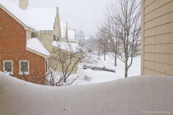 a view of the snow from a second floor window