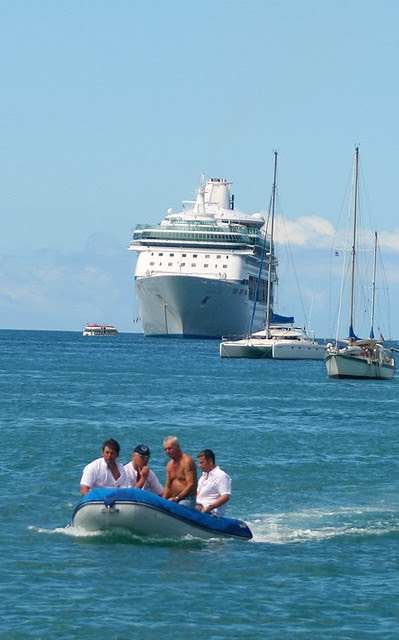 The cruise ship looks grand compared to the other boats!