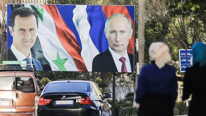 Syrian women walk past a giant poster of President Bashar al-Assad (L) and his Russian counterpart Vladimir Putin (R) in Aleppo (9 March 2017)