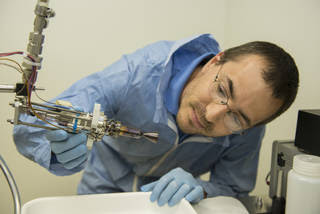 Engineer Chris Burnside examines a smaller 5 Newton thruster that also was tested at NASA's Marshall Space Flight Center.