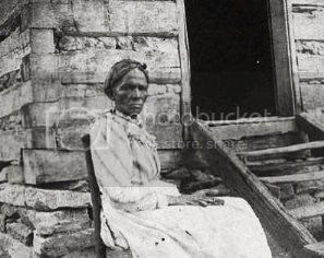 African American woman in front of slave cabin