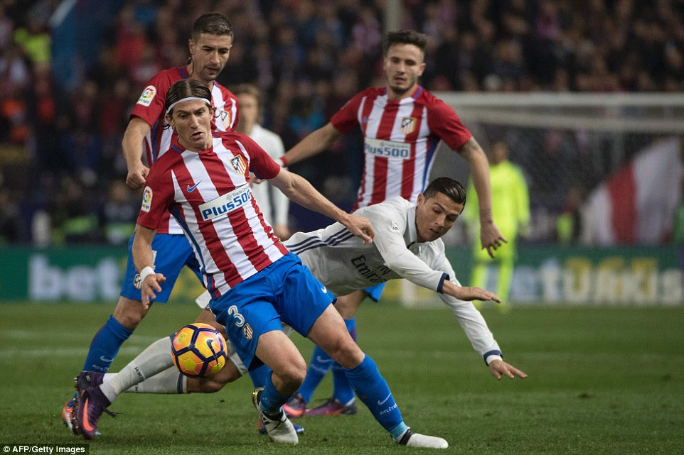 Real Madrid goalscorer Ronaldo takes a tumble under pressure from Atletico Madrid and Brazil full-back Filipe Luis
