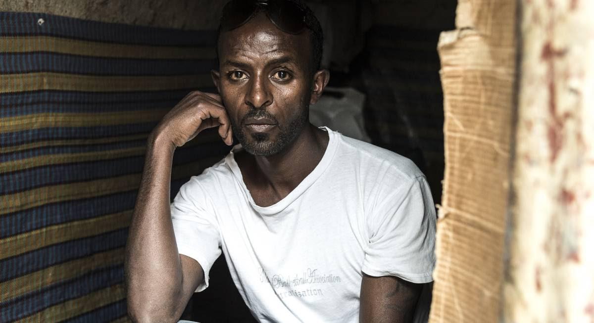 Freu, eritreo de 32 años, en la entrada de la cabaña donde vive en Addis Abeba, Etiopía.