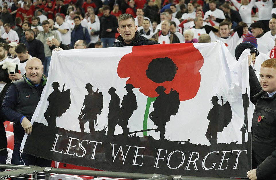 A group of England fans hold up a banner marking Armistice Day ahead of the World Cup qualifier at Wembley