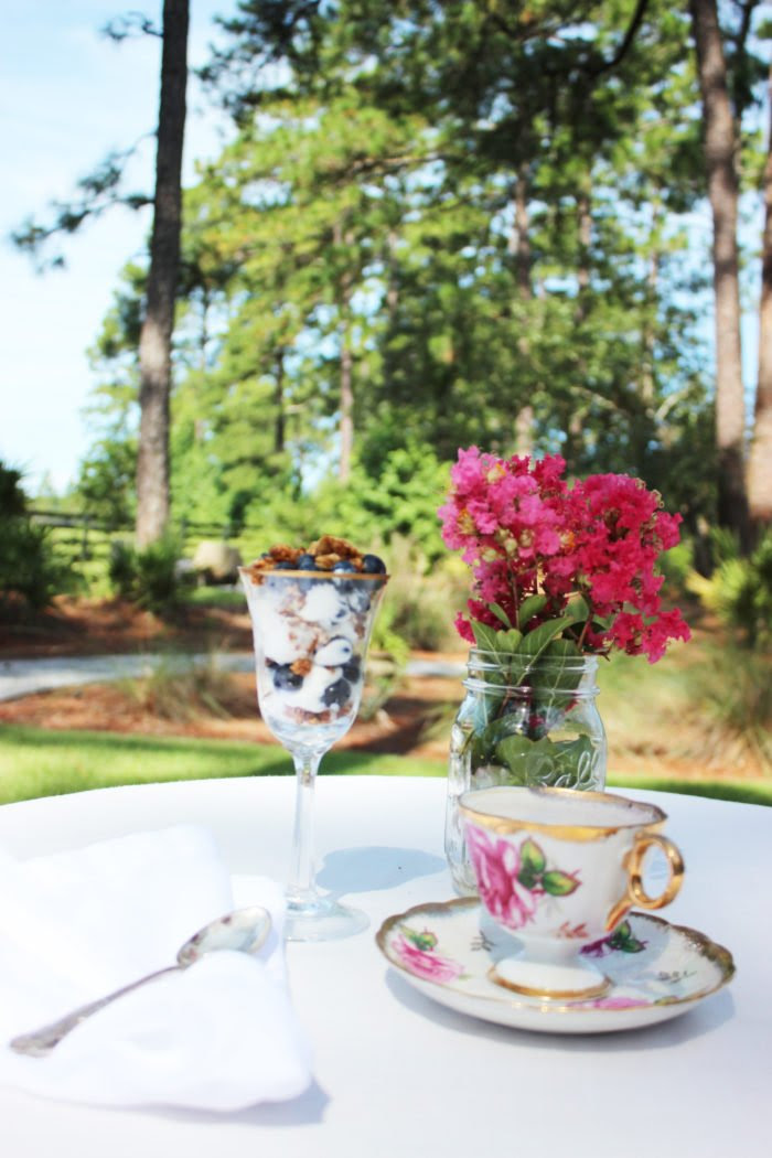 rose tea cup, silver spoon, white table cloth, breakfast outside