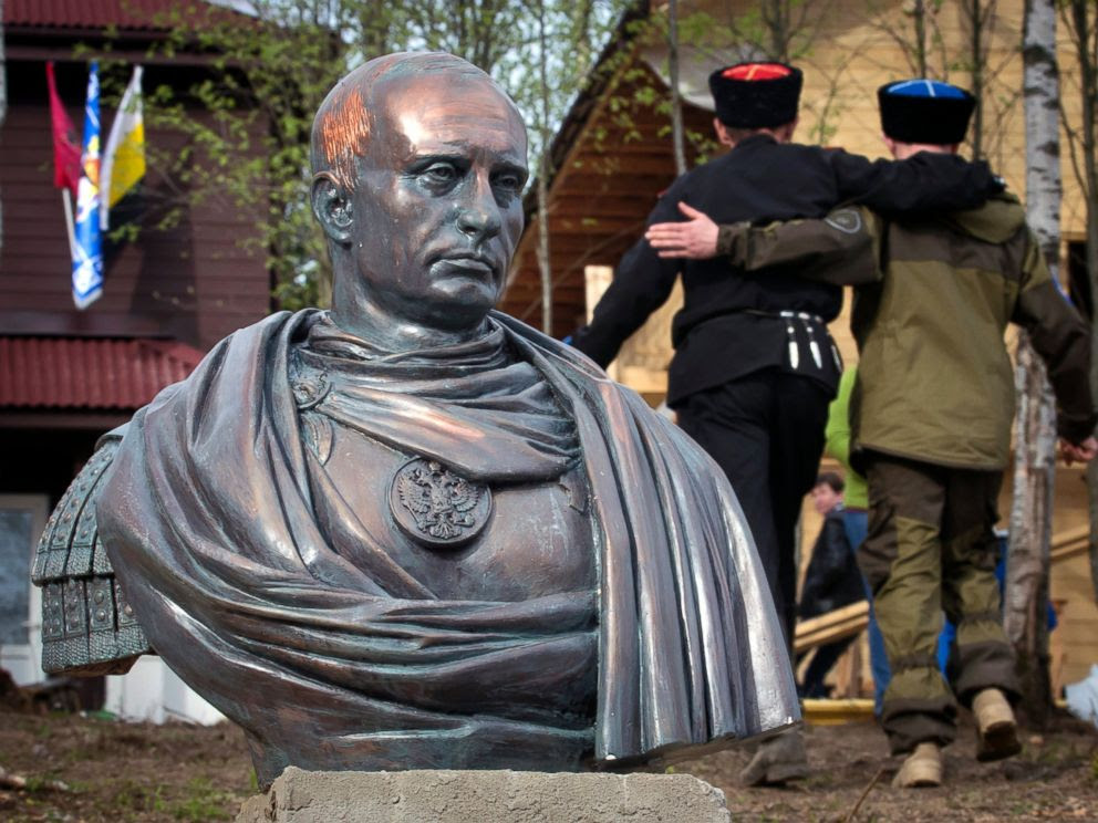 PHOTO: Cossacks walk past a bust of Russian president Vladimir Putin in Kasimovo village, 30 km to the north of St. Petersburg, Russia, May 16, 2015.