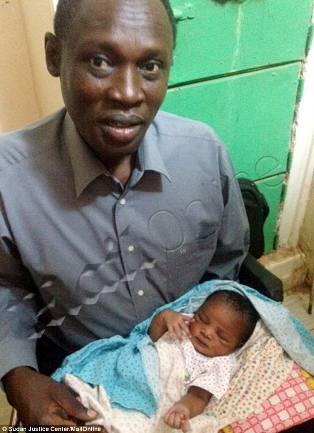 Proud: Father Daniel Wani, a U.S. citizen, from Manchester, New Hampshire, holds Maya for the first time after being allowed to visit to his wife, Meriam Ibrahim, who was sentenced to death for marrying him, a Christian