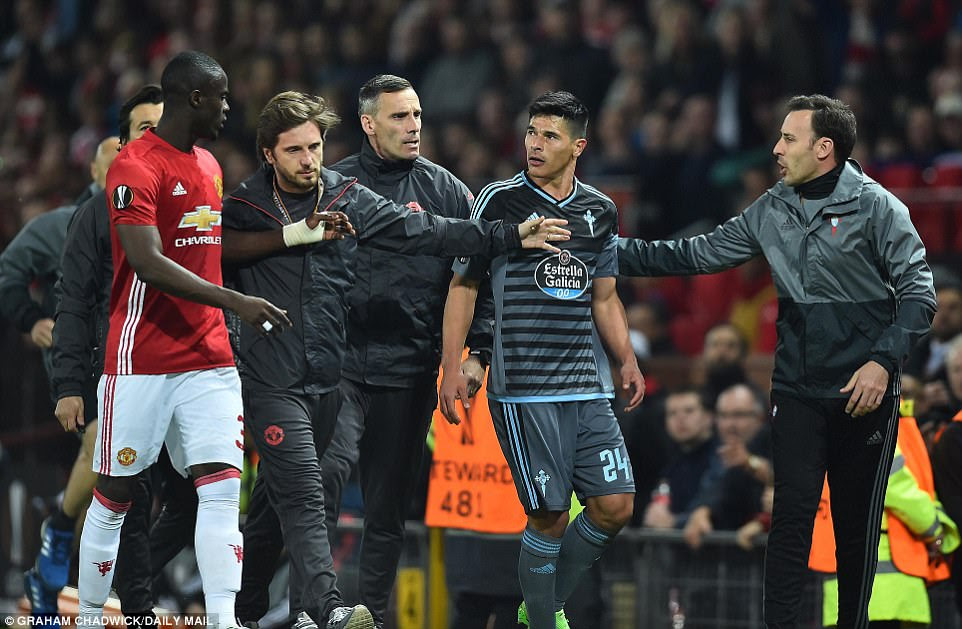 Bailly (left) and Roncaglia (2nd right) continue to argue with each other as they are escorted from the pitch by officials