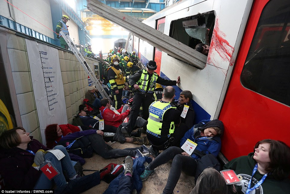 Στο έδαφος: Οι αστυνομικοί παρακολουθούν τη σκηνή του φανταστικού επίθεση, βοηθώντας εκείνους έξω από ένα από τα βαγόνια του μετρό