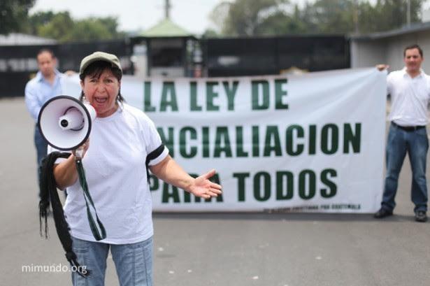 """Ana Virginia Girón, hija de un oficial del ejército asesinado en 1973, se pronuncia fuertemente a favor de Ríos Montt argumentando que el ejército defendió la patria contra los """"guerrilleros terroristas."""" Detrás hay una manta que lee: """"La Ley de Reconciliación es para todos."""""""