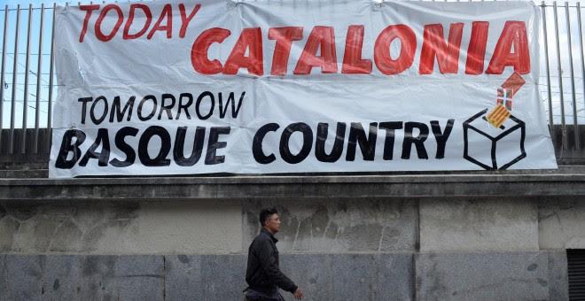 Un hombre pasea a su perro junto a una pancarta en la que se lee 'Hoy, Catalunya, mañana, el País Vasco', en Bilbao, durante la manifestacón por el derecho a decidir organizada por Gure Esku Dago. REUTERS/Vincent West