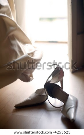 stock photo bridal shoes and wedding dress by the window contra light for