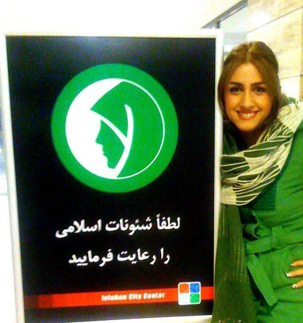 δίπλα σε μια πινακίδα που υπενθυμίζει στις γυναίκες να  συμμορφώνονται με τους κανόνες του ισλάμ