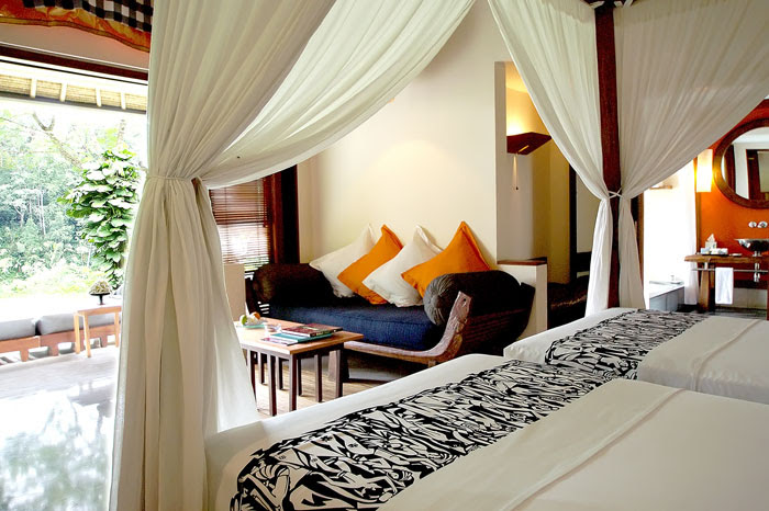 The bedroom in one of the deluxe villas boasts a wall open to the outdoor and furnished in traditional Indonesian decor.