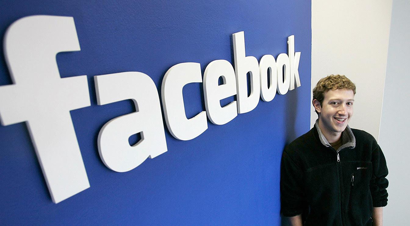 Mark Zuckerberg in front of Facebook logo sign