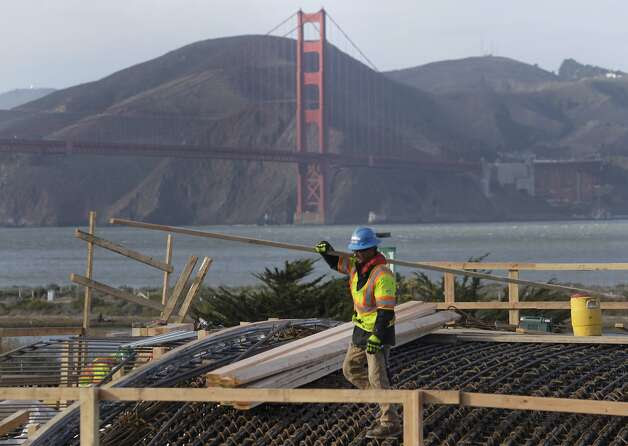 A construction worker carries building material on the roof of the Main Post tunnel for the Presidio Parkway project in San Francisco, Calif. on Thursday, Jan. 30, 2014. The project is on schedule to be completed in 2016. Photo: Paul Chinn, The Chronicle