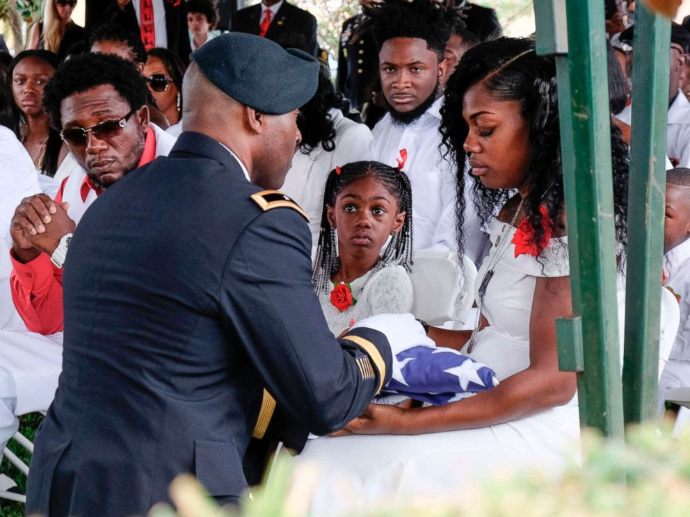 PHOTO: Myeshia Johnson is presented with a folded U.S. flag by a military honor guard member during the burial service for her husband U.S. Army Sgt. La David Johnson at the Memorial Gardens East cemetery, Oct. 21, 2017, in Hollywood, Fla. <p itemprop=