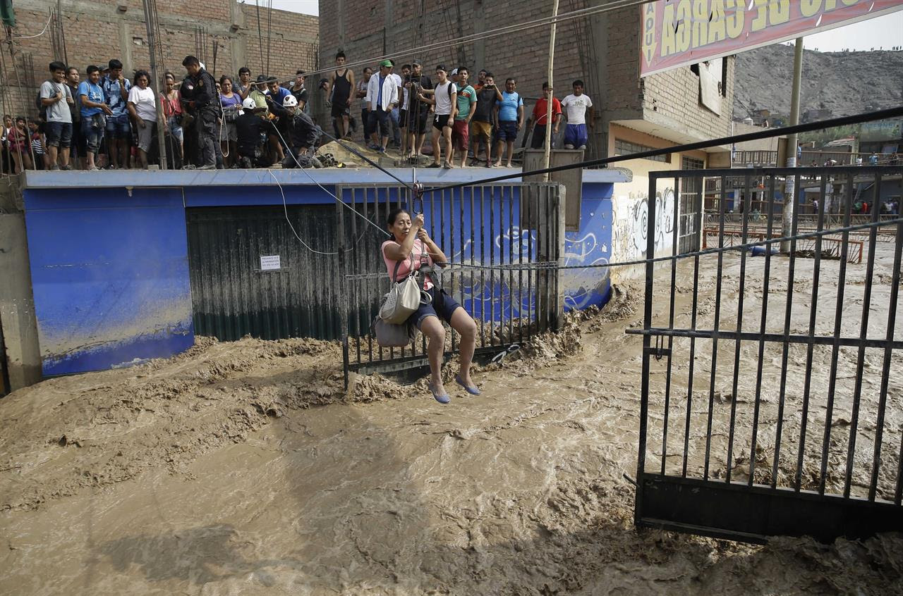 A woman is pulled across flood waters in a zip line harness in Lima, Peru, Friday, March 17, 2017. Intense rains and mudslides over the past three days have wrought havoc around the Andean nation and caught residents in Lima, a desert city of 10 million where it almost never rains, by surprise.