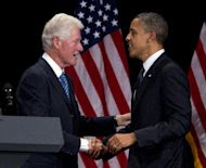 Former President Bill Clinton greets President Barack Obama to speak at a campaign event at the Waldorf Astoria, Monday, June 4, 2012, in New York. (AP Photo/Carolyn Kaster)