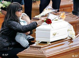 Frau mit Kind vor einem Sarg bei der Trauerfeier (Foto: AP)