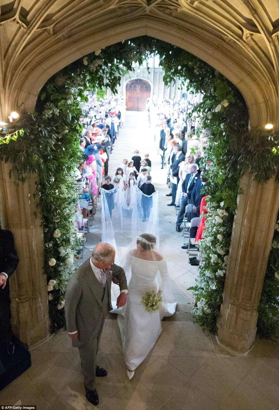 El Príncipe Carlos toma el brazo de Meghan y dice algunas dulces palabras para tranquilizarla mientras toma el lugar de su padre para llevarla por el pasillo