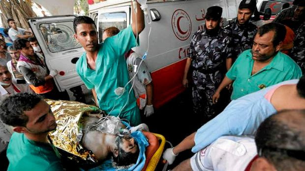 Medics wheel a wounded man into the emergency room at Gaza's Shifa Hospital.