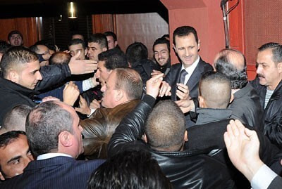 President Bashir al-Assad of Syria is rushed by his supporters after delivering a major address to the embattled nation. The US and other imperialist states are funding and arming agents bent on overthrowing the government. by Pan-African News Wire File Photos