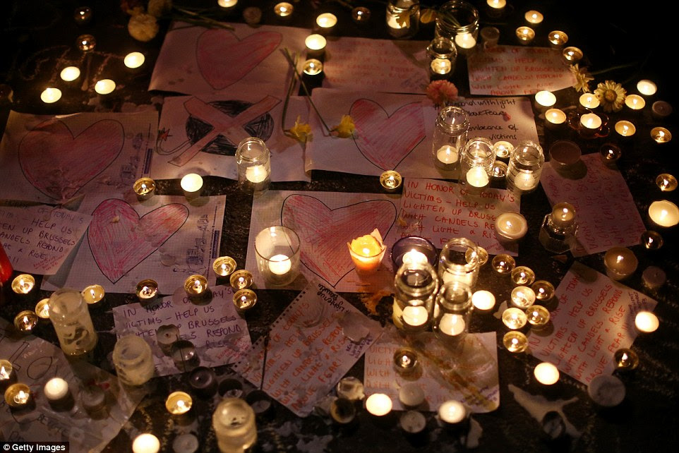 In loving memory: Candles are lit and dozens of touching notes left in honour of the 31 people who were killed in today's Brussels attack