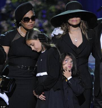 A filha de Michael Jackson, Paris, apoiada em Janet Jackson durante as cerimônias fúnebres de seu pai. Ela alertou para o fato de que seu pai não canta no disco póstumo.