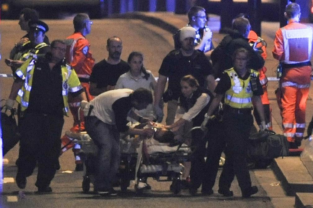 Pessoa ferida é levada em maca por médicos (Foto: DANIEL SORABJI / AFP)