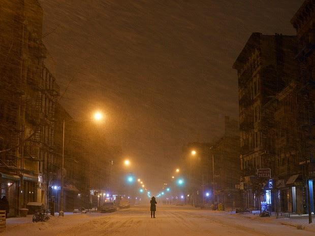 Pessoa caminha no meio da nevasca na Avenida A em East Village na região de Nova York durante a madrugada desta terça-feira (27) (Foto: Patrick Sison/AP Photo)