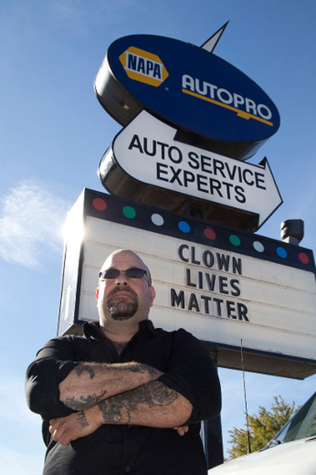 "Napa Autopro supervisor Jon Adler stands by the ""Clown lives matter"" sign posted outside of the shop on Wellington Road. Derek Ruttan/The London Free Press/Postmedia Network"