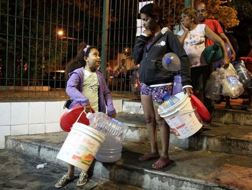Residents of a region that depend on the Cantareira water system, line up to fill water buckets from a public tap at night as the eight-month rationing of water continues as a result of a record drought, in Itu, October 28, 2014.  REUTERS-Nacho Doce