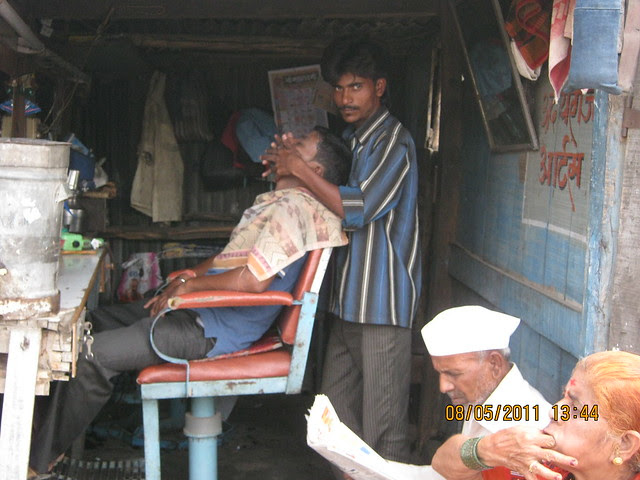 While son is having facial for 40 rupees, father & mother are waiting in the road side saloon in Wagholi - annexe of Kharadi - on Nagar Road near Pune