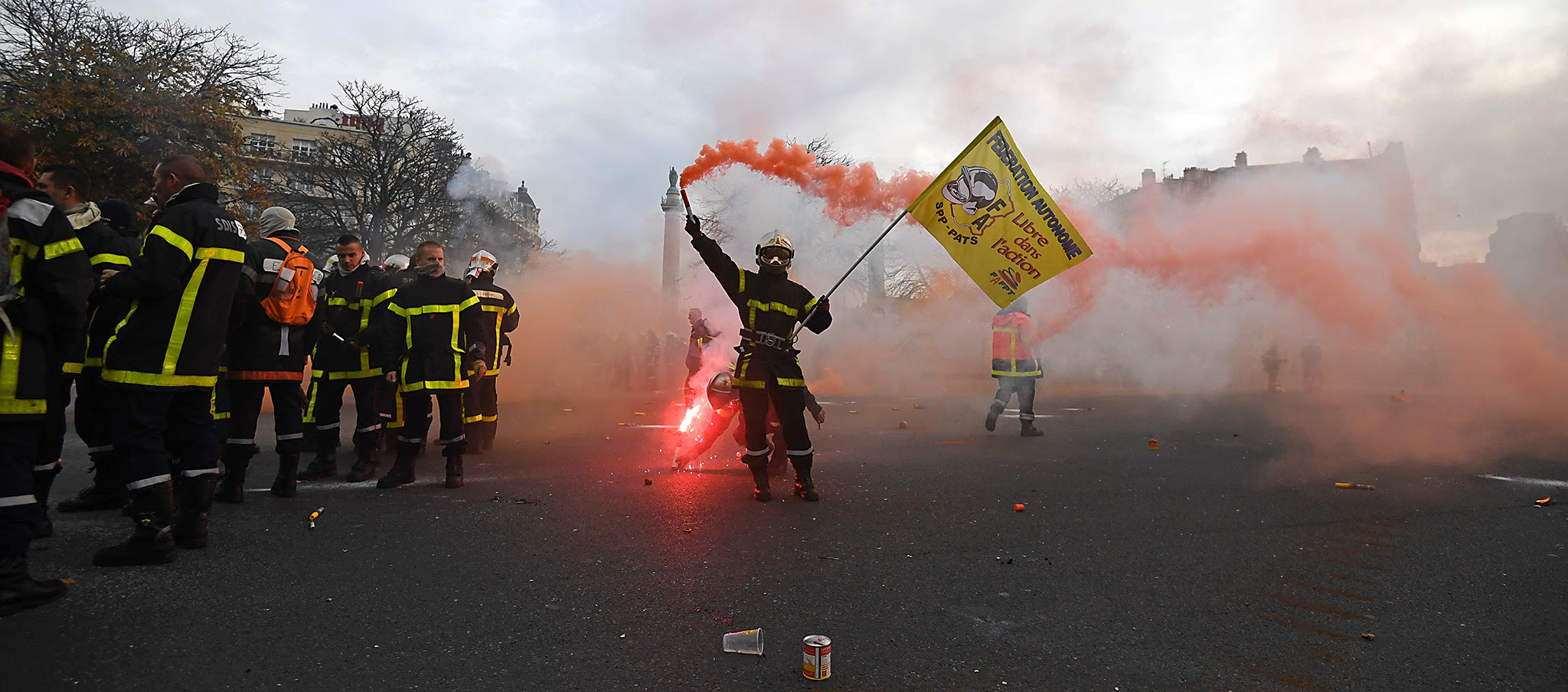 A firefighter brandishes a smoke flares as he and others demonstrate on Place de la Nation in Paris on November 24, 2016 as part of a nationwide strike to denounce violence against firefighters doing their job, budget cuts and downsizing. / AFP PHOTO / ALAIN JOCARDALAIN JOCARD/AFP/Getty Images