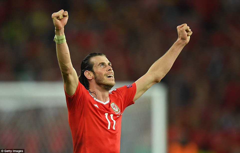 Gareth Bale raises two fists to the heavens after Wales recorded a remarkable 3-1 victory of Belgium to reach the semi-finals