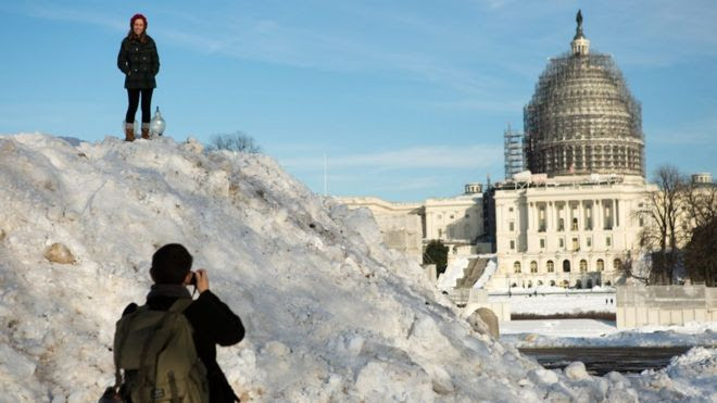 Nicolas Garcia takes a photo of Brienna Harold on top of a snow pile made by snow ploughs in front of the U.S. Capitol building