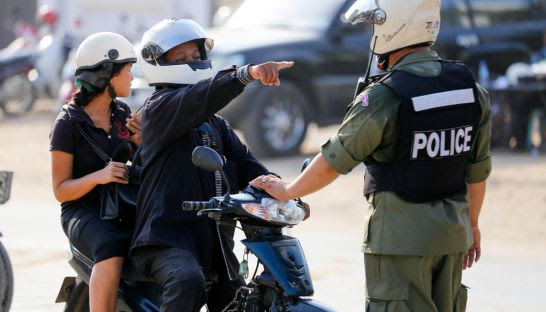 A police officer stops motorists for wearing black earlier this month near Prey Sar Prison during Black Monday protests.