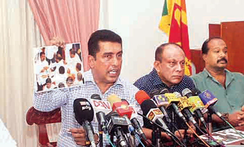 Consumer, Cooperative Development and Christian Religious Affairs Minister Johnston Fernando shows the photos of the two MPs who held knifes. Picture by Sudam Gunasinghe