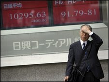 A man waits to cross a street outside a securities firm in Tokyo