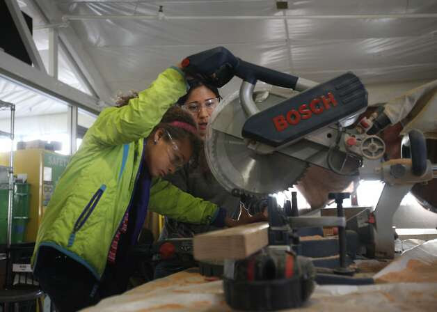 Mikaela James, 9, gains guidance from architect Emily Pilloton while using a miter saw during a class on how to fix things. Photo: Leah Millis, The Chronicle