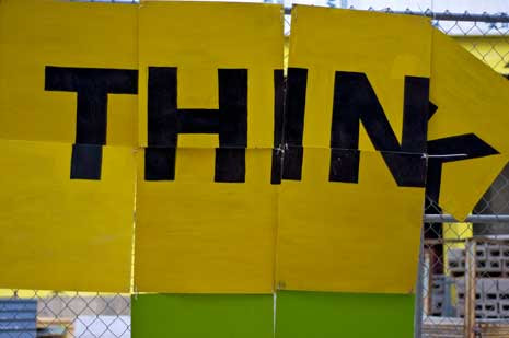 The word Think spelled out in boards attached to a gate, with the K about to fall down