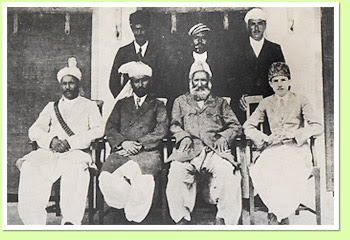 BADSHAH MIANGUL GUL-SHAHZADA, RULER OF SWAT WITH SON AND CHIEF ATTENDENTS. Seated from left to right: Sipah Salar Ahmad Ali, Wazir Hazrat Ali, Badshah Miangul Gul-Shahzada Ruler of Swat, Shahzada Miangul Jahanzeb. Standing: Attaullah Khan, Raja Shah Alam, Abdul Latif Khan.