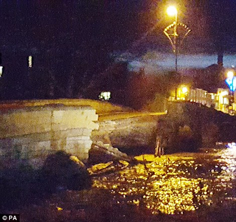 Going, going, gone: A crowd gathered in Tadcaster as stone could be heard falling into the water and creaking noises could be heard