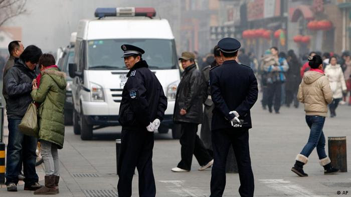 "Chinese police officers stand watch near a McDonald's restaurant which was a planned protest site for ""Jasmine Revolution"" in Beijing, China, Sunday, Feb. 20, 2011. Jittery Chinese authorities staged a concerted show of force Sunday to squelch a mysterious online call for a ""Jasmine Revolution"" apparently modeled after pro-democracy demonstrations sweeping the Middle East. (AP Photo/Andy Wong)"